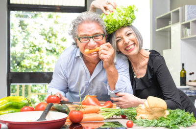Senior couple having fun in kitchen with healthy food - Retired people cooking meal at home with man and woman preparing lunch with bio vegetables - Happy elderly concept with mature funny pensioner